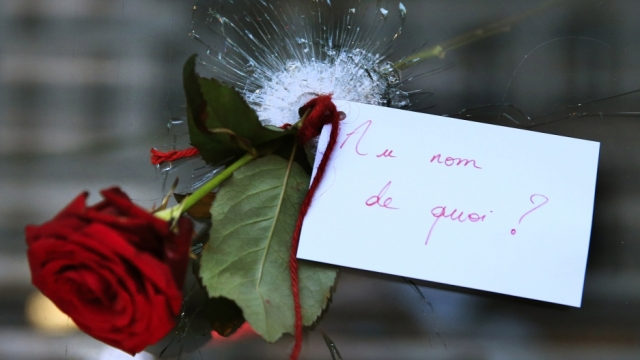 """A rose placed in a bullet hole in a restaurant window the day after a series of deadly attacks in Paris. The note reads """"In the Name of What?"""" Credit: Pascal Rossignol/Reuters"""